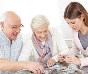 An older couple and a nurse working on a puzzle