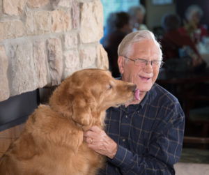 Grappa, a dementia therapy dog, sitting with a senior man